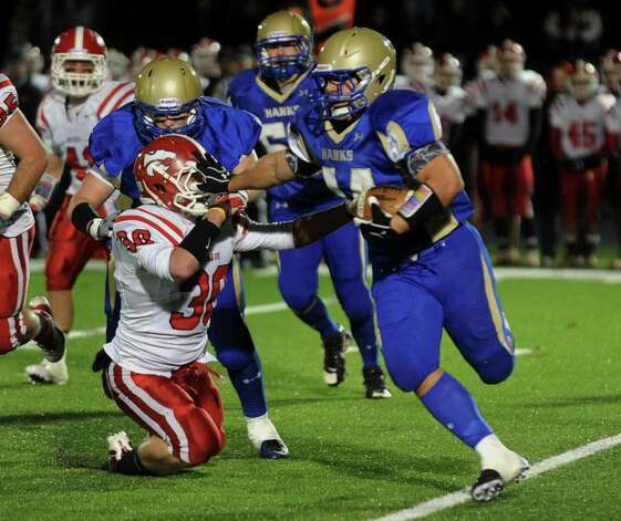 Newtown #44 Louis Fenaroli pushes away Masuk's #30 Pat Tripodi as he carries the ball, during boys football action in Newtown, Conn. on Wednesday November 23, 2011. Photo: Christian Abraham / Connecticut Post