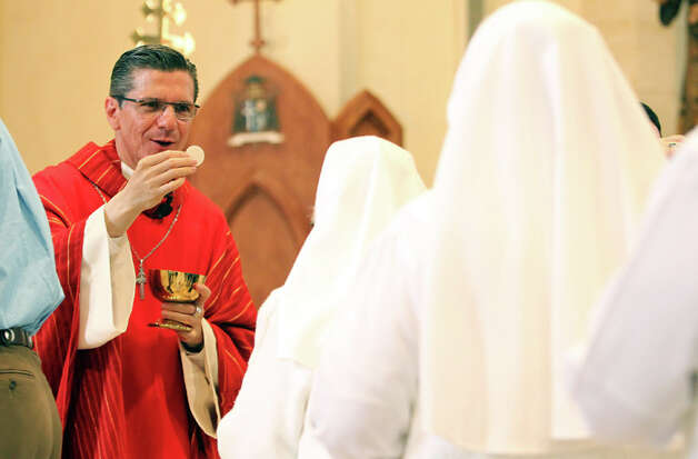 San Antonio Archbishop Gustavo Garcia-Siller performs Communion as he marks his one-year anniversary as head of the Archdiocese of San Antonio. Garcia-Siller presided over the noon Mass at San Fernando Cathedral on Nov. 23, 2011. Photo: KIN MAN HUI, Kin Man Hui/kmhui@express-news.net / SAN ANTONIO EXPRESS-NEWS