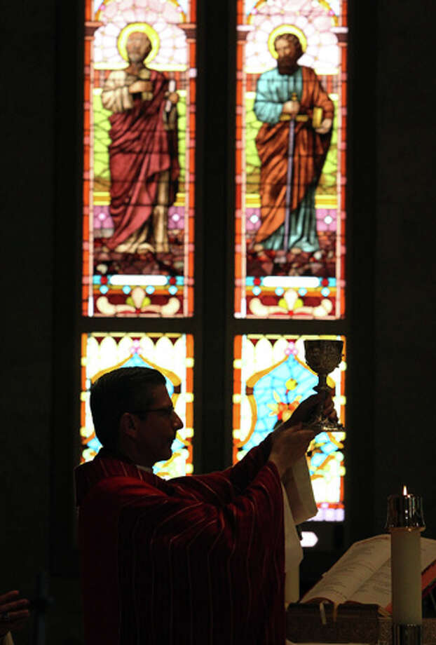 San Antonio Archbishop Gustavo Garcia-Siller presents the Communion chalice during noon Mass at San Fernando Cathedral on Nov. 23, 2011. Garcia-Siller marks his one-year anniversary as head of the Archdiocese of San Antonio. Photo: KIN MAN HUI, Kin Man Hui/kmhui@express-news.net / SAN ANTONIO EXPRESS-NEWS