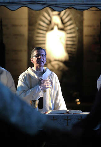 Archbishop Gustavo Garcia-Siller delivers an All Souls Day Mass at San Fernando Cemetery No. 2 on  Nov. 2, 2011. Hundreds of family members of the departed attended the mass and paid homage to their loved ones at the cemetery. Photo: Kin Man Hui, Kin Man Hui/kmhui@express-news.net / San Antonio Express-News