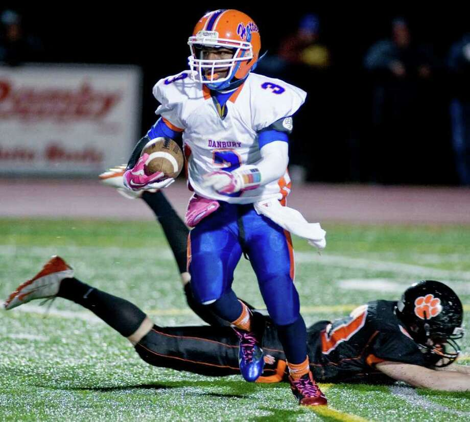 Danbury High School's James Harrington gets through a Ridgefield tackle attempt  during a football game played at Ridgefield High School. Wednesday, Nov. 23, 2011 Photo: Scott Mullin / The News-Times Freelance