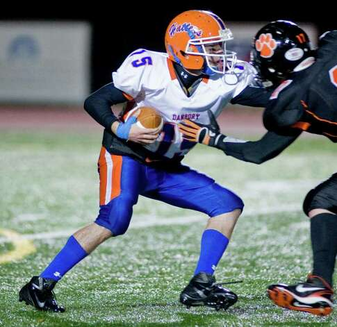 Danbury High School quarterback Garin Mooney tries to get away during a football game against Ridgefield High School, played at Ridgefield. Wednesday, Nov. 23, 2011 Photo: Scott Mullin / The News-Times Freelance