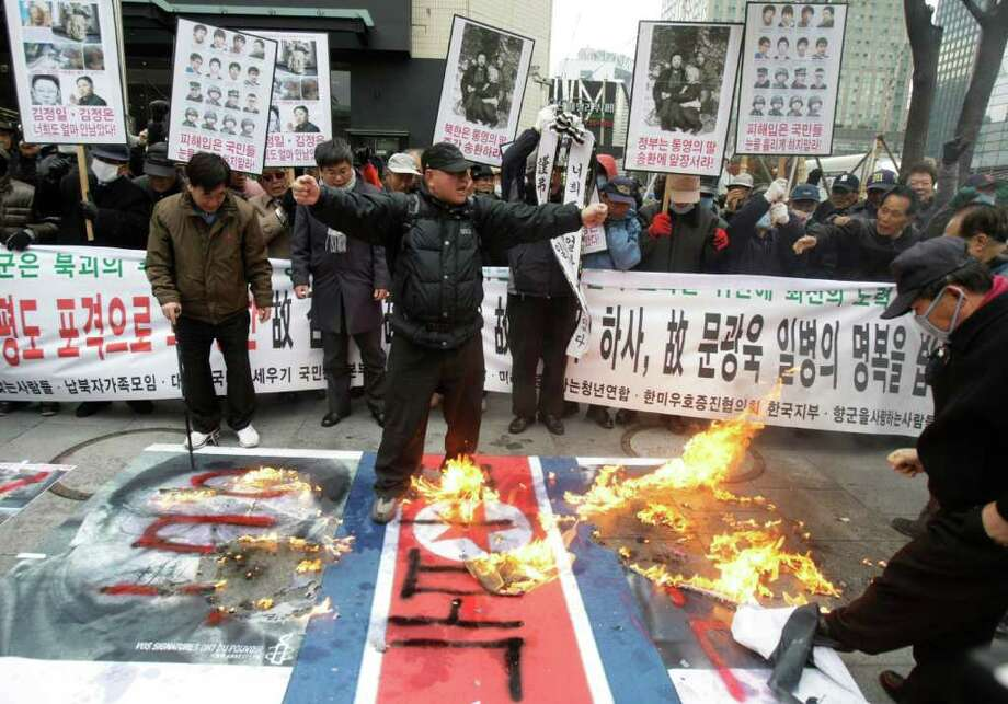 South Korean protesters burn a North Korean flag and pictures of North Korean leader Kim Jong Il, left,  and his son Kim Jong Un, right, during a rally to mark the first anniversary of North Korea's artillery attack on Yeonpyeong Island, in Seoul, South Korea, Wednesday, Nov. 23, 2011. Photo: Ahn Young-joon, Associated Press / AP