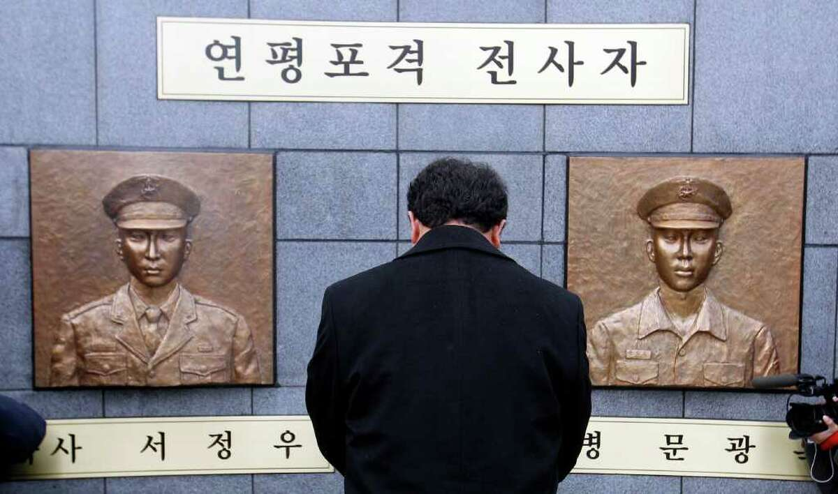 A man pays a silent tribute in front of two bust sculptures of two killed marines during a memorial service on Yeonpyeong Island, South Korea, Wednesday, Nov. 23, 2011. South Korea marked the first anniversary of North Korea's deadly artillery attack on the front-line island Wednesday.