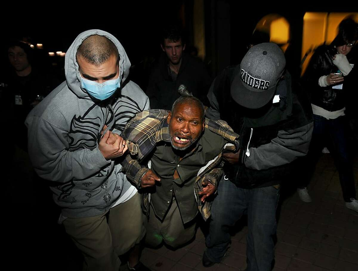 Protesters help an injured Occupy Oakland demonstrator after a police-fired projectile struck his leg on Thursday, Nov. 3, 2011, in Oakland, Calif. Following a mainly peaceful day-long protest by thousands of anti-Wall Street demonstrators, several hundred rallied through the night with some painting graffiti, breaking windows and setting file to garbage cans. (AP Photo/Noah Berger)
