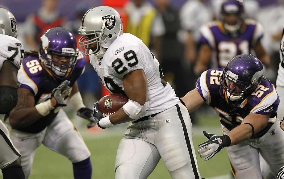 Oakland Raiders running back Michael Bush (29) runs from Minnesota Vikings defenders E.J. Henderson, left, and Chad Greenway, right, during the second half of an NFL football game Sunday, Nov. 20, 2011, in Minneapolis. (AP Photo/Andy King) Photo: Andy King, AP