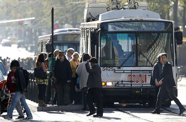 A pair of MUNI buses make a stop along Market Street on Thursday November 10, 2011 in San Francisco, Ca. The Municipal Transportation Agency is facing a $34 million deficit for next year and a $46 million deificit for the following year. Ideas to help erase that gap include charging riders who pay cash fares an extra 25 cents, and another 25 cents on top of that if they use a transfer. Also being considered is making drivers pay $3 more for parking fines and having parking meters fed on Sundays and later into the evenings. Photo: Michael Macor, The Chronicle