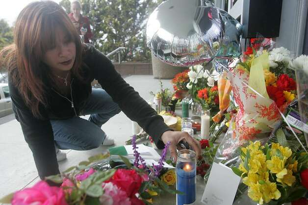 Gayle Cordero places a candle at a memorial for slain police officer James Capoot in front of the police department on Friday, Nov. 18, 2011, in Vallejo, Calif. Capoot was fatally shot by a bank robbery suspect on Thursday. Photo: Mathew Sumner, Special To The Chronicle