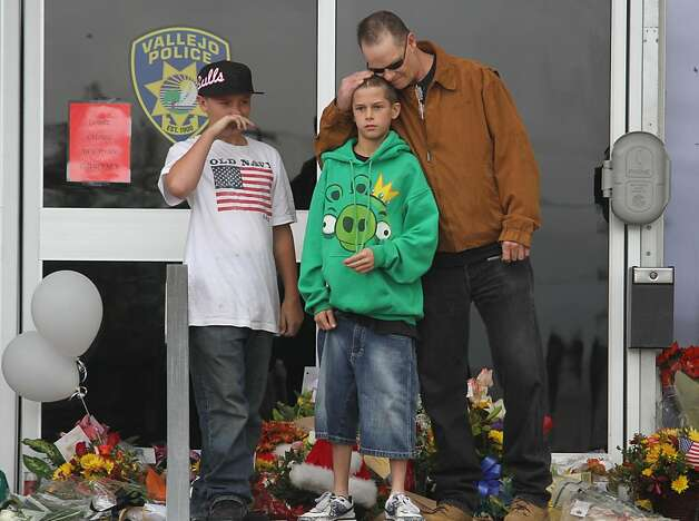 Roy Wright comforts his son Justin Wright, 11, at a memorial for slain police officer James Capoot in front of the police department on Friday, Nov. 18, 2011, in Vallejo, Calif. Capoot was fatally shot by a bank robbery suspect on Thursday. Capoot had visited the Wright family the night before his death to talk with Justin about being good and doing well in school. Photo: Mathew Sumner, Special To The Chronicle