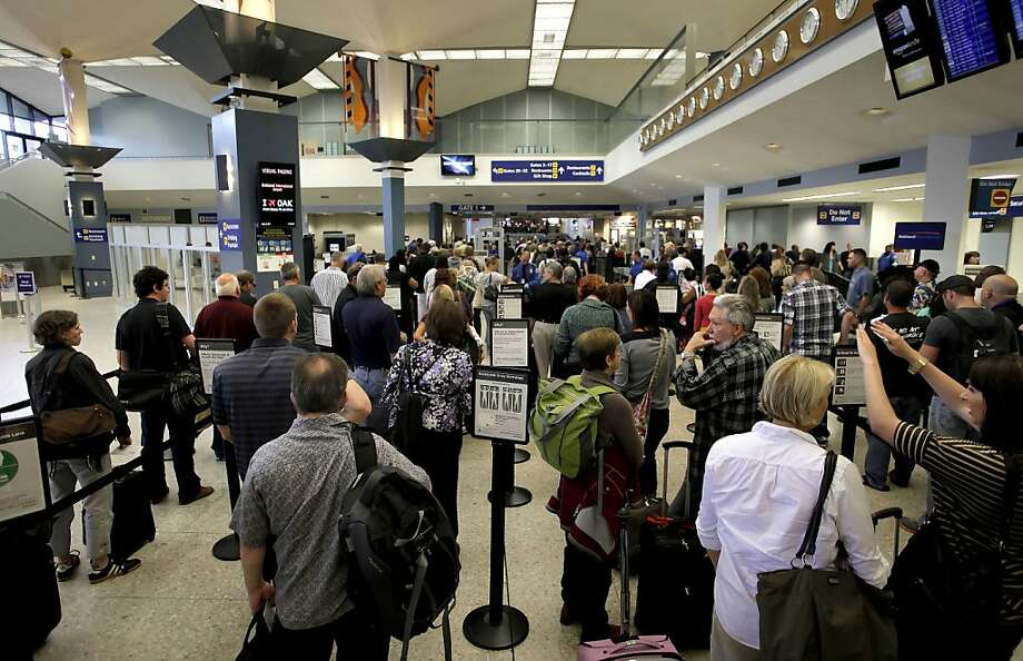 Passengers line up at the TSA security checkpoint as Terminal 1 is reopened. A suspicious device was discovered in a backpack while the TSA was operating the security checkpoint in Terminal 1 of the Oakland International Airport, on Friday August 12, 2011, in Oakland, Ca. Terminal 1 was shut down for one and a half hours, as the Alameda County Bomb Squad discovered the device to be harmless, revealing a pump for an air mattress and an illegal volume of liquid, (over 3 ozs.), the area was reopened shortly thereafter. Photo: Michael Macor, The Chronicle