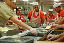 Inmates including Wilfred Marrero (center) work together to make lunch trays for fellow inmates in the Bexar County Jail on Wednesday, Nov. 23,  2011.
