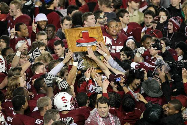 Members of the Stanford Cardinal football team along with students reach for the Axe after defeating the University of California in the 114th annual Big Game  at Stanford Stadium 31-28 November 19, 2011 in Stanford, California. Photo: Lance Iversen, The Chronicle