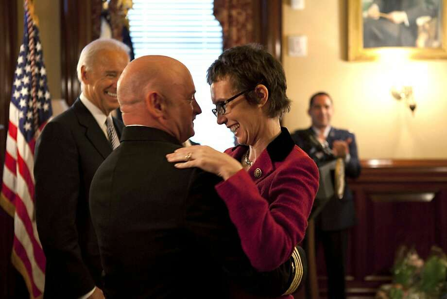 In this image released by the White House, Navy Capt. Mark Kelly hugs his wife Rep. Gabrielle Giffords, D-Ariz., after he received the Legion of Merit from Vice President Joe Biden during Kelly's retirement ceremony in the Secretary of War Suite in the Eisenhower Executive Office Building on the White House complex in Washington, Thursday, Oct. 6, 2011. (AP Photo/The White House, David Lienemann) Ran on: 10-07-2011 Please insert a phrase related to shooting to provide context for reader Rep. Gabrielle Giffords, D-Ariz., recovering from a shot to the head by a gunman in Tucson in January, is hugged by husband, Navy Capt. Mark Kelly, after he received the Legion of Merit from Vice President Joe Biden (left) during his retirement ceremony in Washington. Photo: David Lienemann, AP