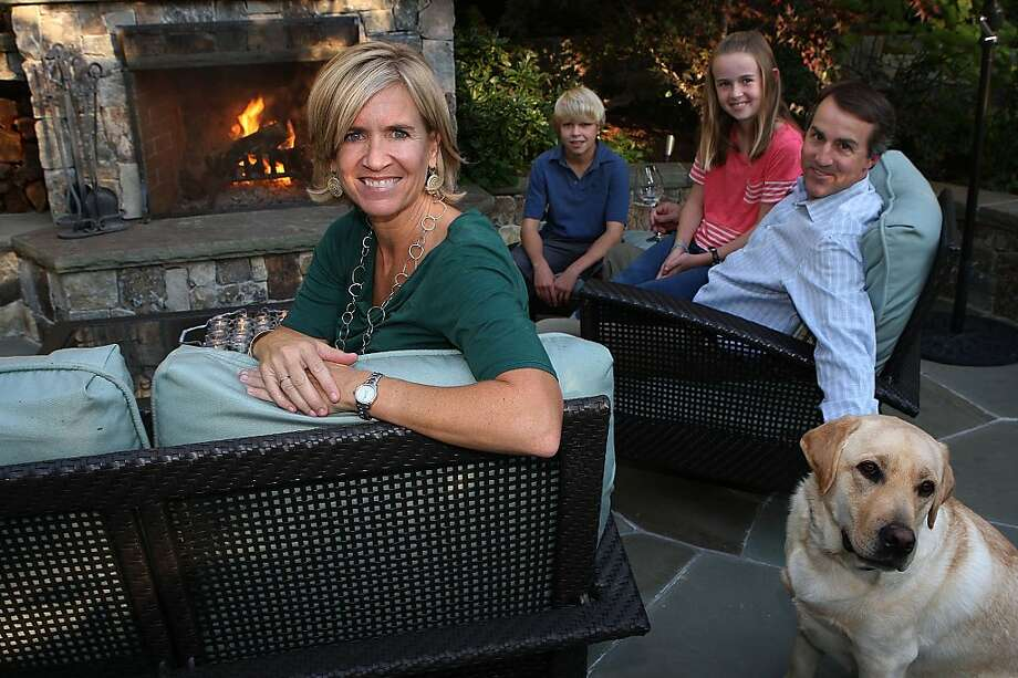 Valerie Herzog (left) with her family Jack Herzog, 14 years old, Megan Herzog, 11 years old,  and husband Paul Herzog with Colby on their patio deck in front of their outside fireplace in Ross, Calif., on Friday, October 28, 2011. Photo: Liz Hafalia, The Chronicle