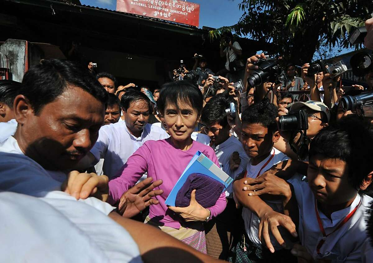 Democracy icon Aung San Suu Kyi (C) leaves the National League for Democracy party (NLD) offices after a meeting in Yangon on November 18, 2011. Suu Kyi's opposition party in Myanmar announced on November 18 that it would re-register as a political party and take part in upcoming by-elections, after years of marginalisation. TOPSHOTS AFP PHOTO / Soe Than WIN (Photo credit should read Soe Than WIN/AFP/Getty Images)