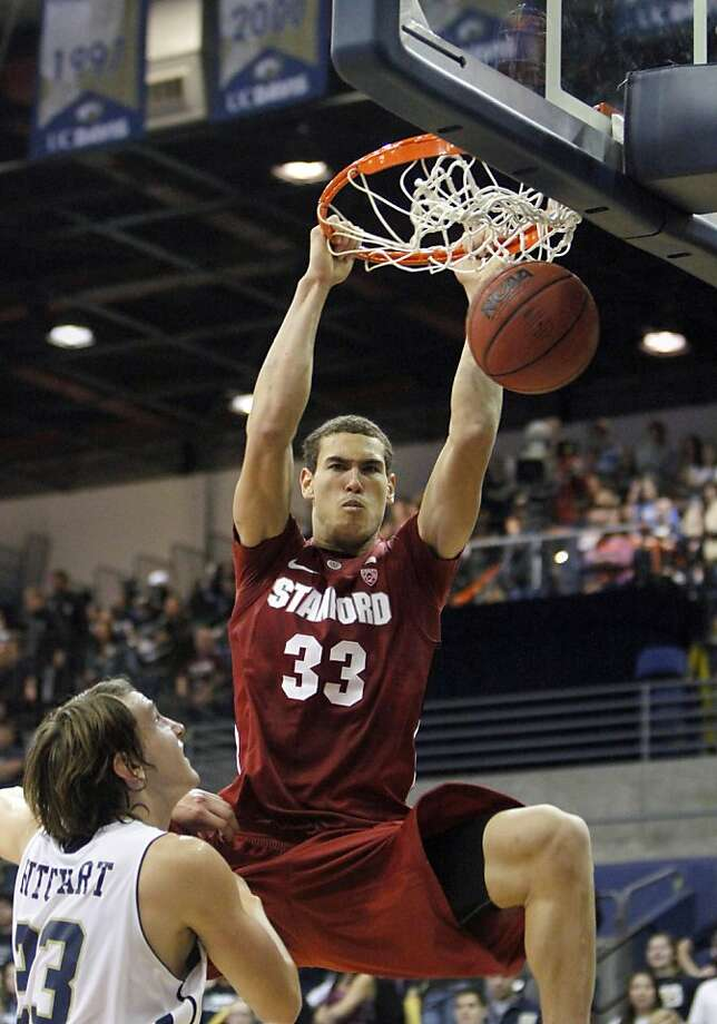 Stanford forward Dwight Powell, right,  hangs on the rim after stuffing over U.C. Davis forward Josh Ritchart, during the second half of NCAA college basketball in Davis, Calif., Friday, Nov. 18, 2011.  Stanford won 70-49. (AP Photo/Rich Pedroncelli)  Ran on: 11-19-2011 Dwight Powell slams home two of his 13 points. UC Davis' Josh Ritchart (left) had a game-high 19. Photo: Rich Pedroncelli, AP