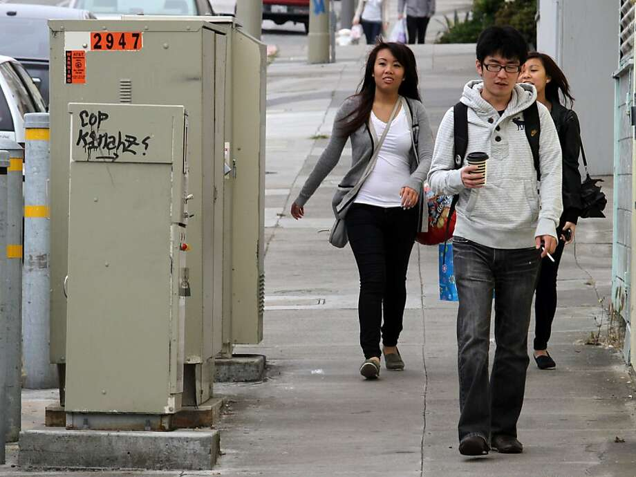 Pedestrians pass by a line of utility boxes lines Taraval St. at 40th Ave. in the Sunset. Ran on: 08-01-2011 Pedestrians pass a row of utility boxes on Taraval Street at 40th Avenue in S.F. Photo: Mathew Sumner, Special To The Chronicle