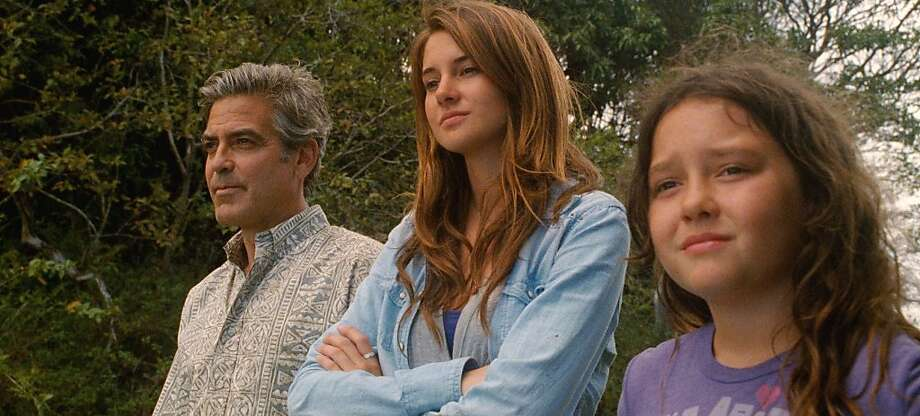L to R: George Clooney as ÒMatt King,Ó Shailene Woodley as ÒAlexandra,Ó and Amara Miller as ÒScottieÓ star in THE DESCENDANTS. Photo: Fox Searchlight