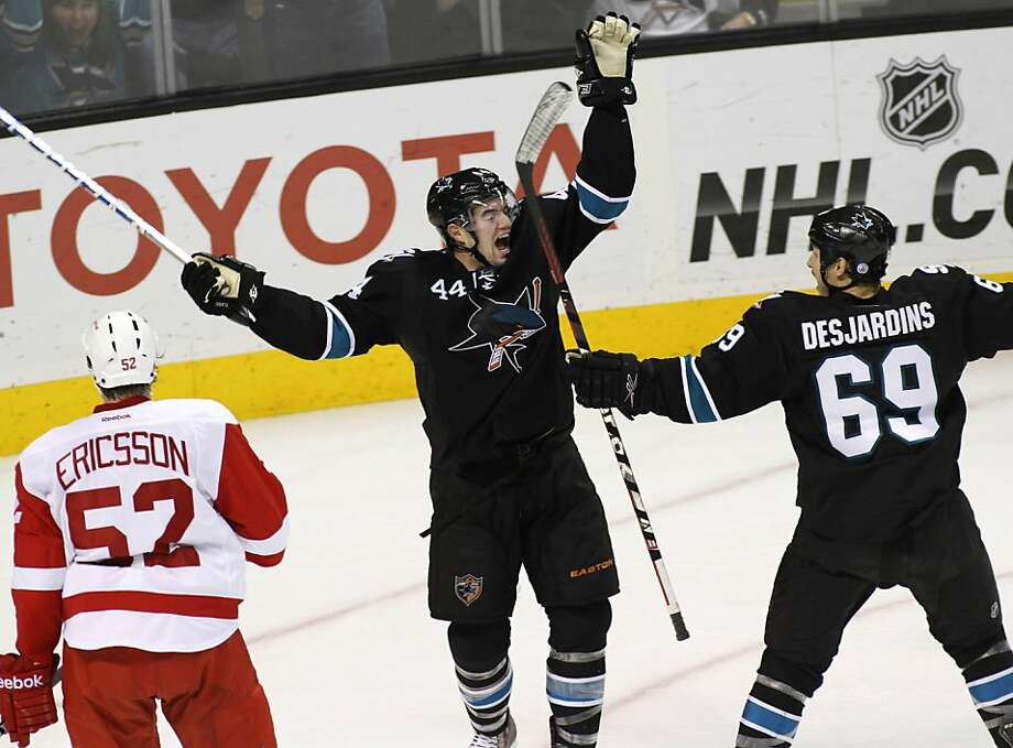 San Jose Sharks'  Marc-Edouard Vlasic, center, celebrates with teammate Andrew Desjardins, right, after scoring a goal against the Detroit Red Wings during the second period of an NHL hockey game, Thursday, Nov. 17, 2011 in San Jose, Calif. At left is Red Wings' Jonathan Ericsson. (AP Photo/George Nikitin)  Ran on: 11-18-2011 Marc-Edouard Vlasic (44) celebrates his second-period goal with Andrew Desjardins after giving the Sharks a 3-1 lead. Vlasic also had three assists in San Jose's win. Photo: George Nikitin, AP