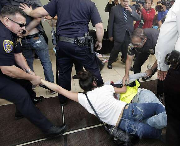 Student demonstrators are shown being removed by Long Beach Police officers during a protest Wednesday Nov. 16, 2011 at the California State University Board of Trustees meeting in Long Beach, Calif. A struggle erupted between demonstrators and police Wednesday as trustees of the huge CSU system met to vote for another tuition hike, this time a 9 percent increase. (AP Photo/Nick Ut) Photo: Nick Ut, AP
