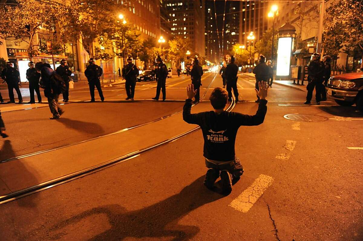 A protester is seen on his knees in front of police officers who are blocking the street where a raid was taking place at Occupy San Francisco on November 16, 2011.