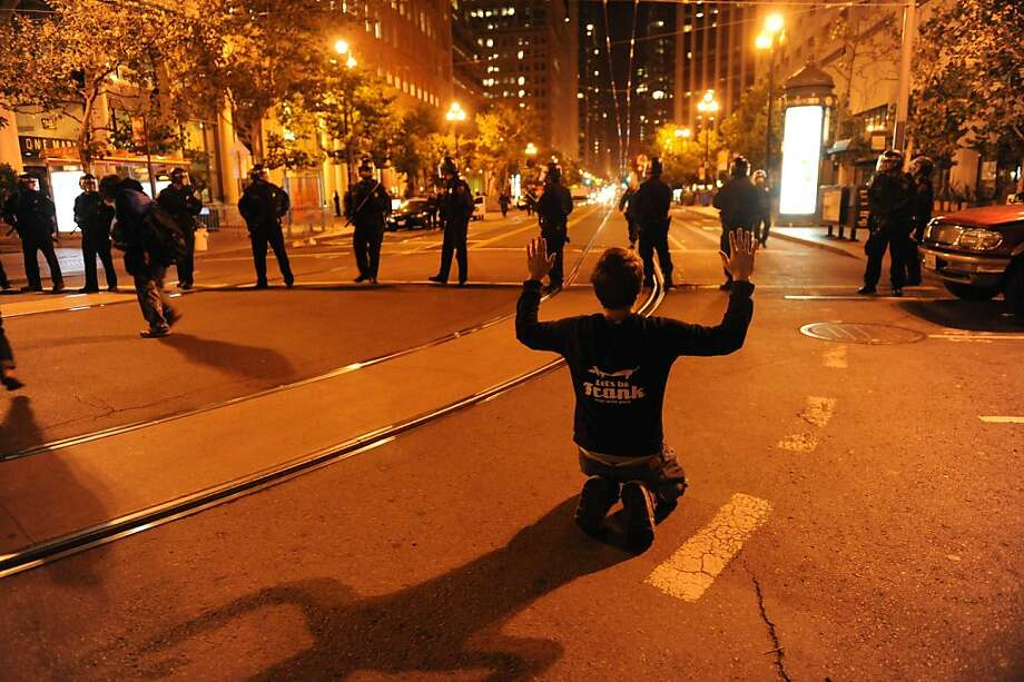 A protester is seen on his knees in front of police officers who are blocking the street where a raid was taking place at Occupy San Francisco on November 16, 2011. Photo: Susana Bates, Special To The Chronicle