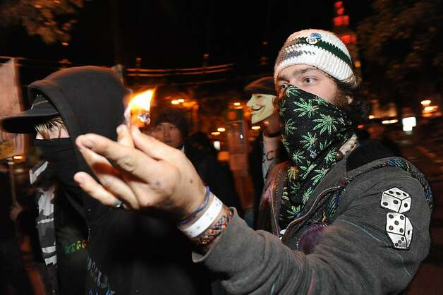 A protester burns a dollar bill at Occupy San Francisco on November 16, 2011. Earlier in the morning police raided a stretch of 15 tents on Market Street. Photo: Susana Bates, Special To The Chronicle