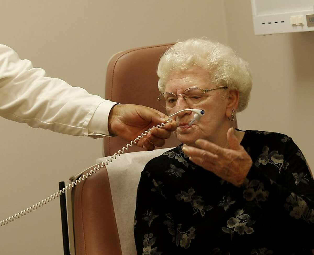 In the lung clinic, Carol Paule gets her temperature checked by Dr. Abid Majid. Doctors Medical Center in San Pablo, Calif. is in danger of closing down services if a parcel tax is not passed by voters Tuesday November 15, 2011.