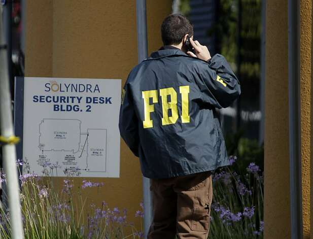 A federal agent talks on his phone after authorities from the FBI and Department of Energy served search warrants at the Solyndra solar company in Fremont, Calif. on Thursday, Sept. 8, 2011. Last week, Solyndra laid off all of its 1,100 employees after filing for bankruptcy.   Ran on: 09-11-2011 Federal agents raid defunct solar plant Solyndra in Fremont. Photo: Paul Chinn, The Chronicle