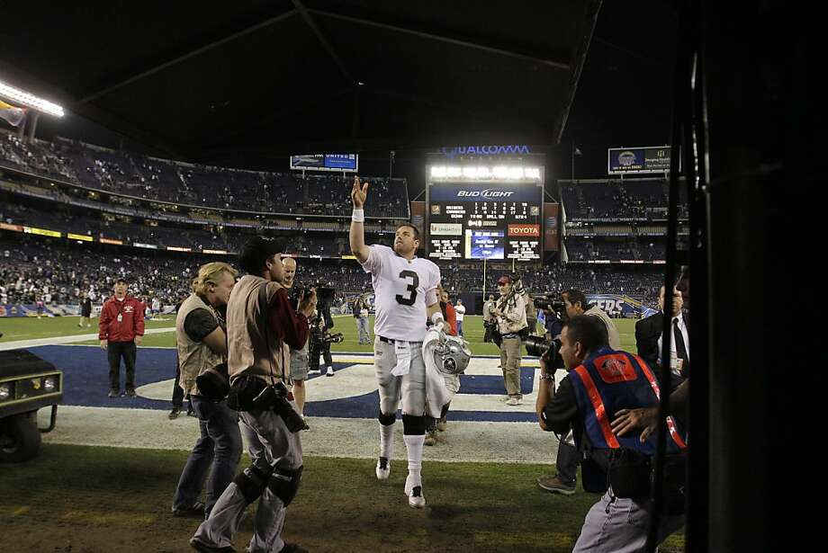 Oakland Raiders quarterback Carson Palmer throws his hat to a fan after defeating the San Diego Chargers 24-17 in an NFL football game  Thursday, Nov. 10, 2011, in San Diego. (AP Photo/Gregory Bull)   Ran on: 11-16-2011 Things are looking up for Carson Palmer and the Raiders after Oakland prevailed in San Diego. Photo: Gregory Bull, AP