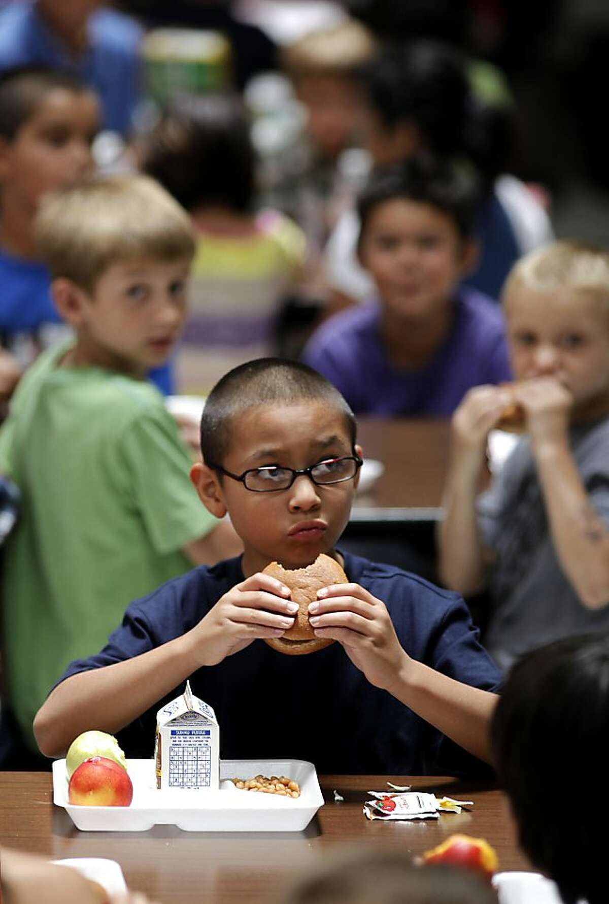 Third garder, Steven enjoys his burger with a whole grain bun during lunch at the Sisk Elementary school have lunch in Salida, Ca. on Wednesday August 10, 2011. Billy Reid a former French chef is now the the head of the Salida schools meal program, which makes the daily school lunch program healthy and delicious. Ran on: 09-05-2011 A third-graders burger has a whole grain bun at Sisk Elementary in Salida (Stanislaus County). Ran on: 09-05-2011 A Sisk Elementary third-grader eats a burger on a whole-grain bun in Salida (Stanislaus County).