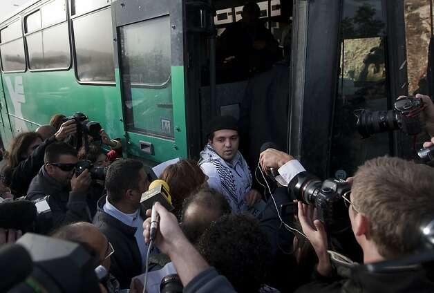 "Reporters surround a Palestinian activist as he boards an Israeli bus outside the West Bank Jewish settlement of Migron, near Ramallah, on November 15, 2011. Palestinian ""Freedom Riders"" reenacted US civil rights movement's boarding of segregated buses in the American south by riding Israeli settler buses to Jerusalem. Several Israeli transportation companies operate dozens of lines that run through the occupied West Bank and east Jerusalem, many of them subsidized by the state. While it is not officially forbidden for Palestinians to use Israeli public transportation in the West Bank, these lines are effectively segregated, since many of them pass through Jewish-only settlements, to which Palestinian entry is prohibited by a military decree.    AFP PHOTO/AHMAD GHARABLI (Photo credit should read AHMAD GHARABLI/AFP/Getty Images) Photo: Ahmad Gharabli, AFP/Getty Images"