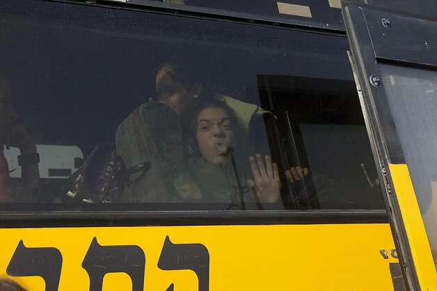 "A young Israeli settler grimaces from inside a bus as media and Palestinian activists gather at a bus stop outside the West Bank Israeli settlement of Migron, near Ramallah, on November 15, 2011. Palestinian ""Freedom Riders"" reenacted US civil rights movement's boarding of segregated buses in the American south by riding Israeli settler buses to Jerusalem. Several Israeli transportation companies operate dozens of lines that run through the occupied West Bank and east Jerusalem, many of them subsidized by the state. While it is not officially forbidden for Palestinians to use Israeli public transportation in the West Bank, these lines are effectively segregated, since many of them pass through Jewish-only settlements, to which Palestinian entry is prohibited by a military decree.    AFP PHOTO/AHMAD GHARABLI (Photo credit should read AHMAD GHARABLI/AFP/Getty Images) Photo: Ahmad Gharabli, AFP/Getty Images"