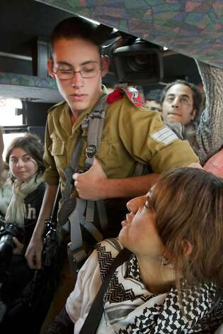 Activist Huwada Aaraf talks to an Israeli soldier who happened to be on the bus as Palestinians today, Tuesday, November 15, 2011, adopted a new tactic in their confrontations with Israeli authorities in the West Bank, boarding buses intended for Jewish settlers in what they say is an effort to emulate the civil rights movement in the United States. Israeli authorities pulled the six riders from the bus when it reached a checkpoint outside Jerusalem. (Maya Levin/MCT) Photo: Maya Levin, MCT