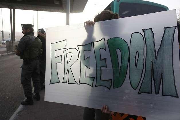 "A protestor holds a sign on November 15, 2011  at the Hizmeh checkpoint between Ramallah and Jerusalem. Six Palestinians were arrested as they tried to enter Jerusalem on an Israeli bus in a novel bid to protest what they call Israel's discriminatory policies in the West Bank. The six activists, five men and one woman, said their protest was inspired by the ""Freedom Riders,"" American civil rights activists who rode to the south in the 1960s to carry out work against segregation and racial discrimination.  AFP PHOTO/AHMAD GHARABLI (Photo credit should read AHMAD GHARABLI/AFP/Getty Images) Photo: Ahmad Gharabli, AFP/Getty Images"