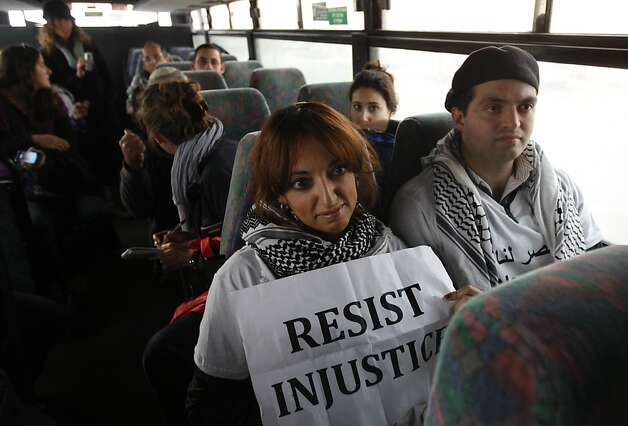"Two Palestinian activists sit inside as Israeli bus as it rides between a bus stop outside the West Bank Jewish settlement of Migron, near Ramallah, and a checkpoint leading to Jerusalem, on November 15, 2011. Palestinian ""Freedom Riders"" reenacted US civil rights movement's boarding of segregated buses in the American south by riding Israeli settler buses to Jerusalem. Several Israeli transportation companies operate dozens of lines that run through the occupied West Bank and east Jerusalem, many of them subsidized by the state. While it is not officially forbidden for Palestinians to use Israeli public transportation in the West Bank, these lines are effectively segregated, since many of them pass through Jewish-only settlements, to which Palestinian entry is prohibited by a military decree.    AFP PHOTO/AHMAD GHARABLI (Photo credit should read AHMAD GHARABLI/AFP/Getty Images) Photo: Ahmad Gharabli, AFP/Getty Images"