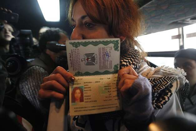 "A Palestinian activist displays her passport as she rides an Israeli bus between a bus stop outside the West Bank Jewish settlement of Migron, near Ramallah, and a checkpoint leading to Jerusalem, on November 15, 2011. Palestinian ""Freedom Riders"" reenacted US civil rights movement's boarding of segregated buses in the American south by riding Israeli settler buses to Jerusalem. Several Israeli transportation companies operate dozens of lines that run through the occupied West Bank and east Jerusalem, many of them subsidized by the state. While it is not officially forbidden for Palestinians to use Israeli public transportation in the West Bank, these lines are effectively segregated, since many of them pass through Jewish-only settlements, to which Palestinian entry is prohibited by a military decree.    AFP PHOTO/AHMAD GHARABLI (Photo credit should read AHMAD GHARABLI/AFP/Getty Images) Photo: Ahmad Gharabli, AFP/Getty Images"