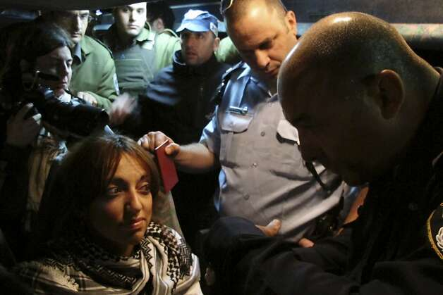 Israeli police officers speaks to Palestinian activist Hawaida Arraf, one of six who boarded a bus belonging to the Israeli bus company Egged, after it reached the Hizma checkpoint before entering Jerusalem, Tuesday, Nov. 15, 2011. Six Palestinian activists, defiantly clutching national flags and surrounded by dozens of reporters, were dragged off an Israeli bus that they were hoping would lead them to Jerusalem, after an hours-long stand off with police on Tuesday. The Palestinians said they boarded the Israeli bus in a widely advertised action, hoping to draw attention what they say are discriminatory measures in the West Bank, particularly travel restrictions.(AP Photo/Diaa Hadid) Photo: Diaa Hadid, AP
