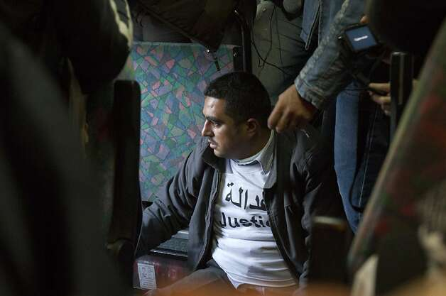an activist who was removed from his seat by boarder guards, sits on the floor of the bus, refusing to move as Palestinians today, Tuesday, November 15, 2011, adopted a new tactic in their confrontations with Israeli authorities in the West Bank, boarding buses intended for Jewish settlers in what they say is an effort to emulate the civil rights movement in the United States. Israeli authorities pulled the six riders from the bus when it reached a checkpoint outside Jerusalem. (Maya Levin/MCT) Photo: Maya Levin, MCT