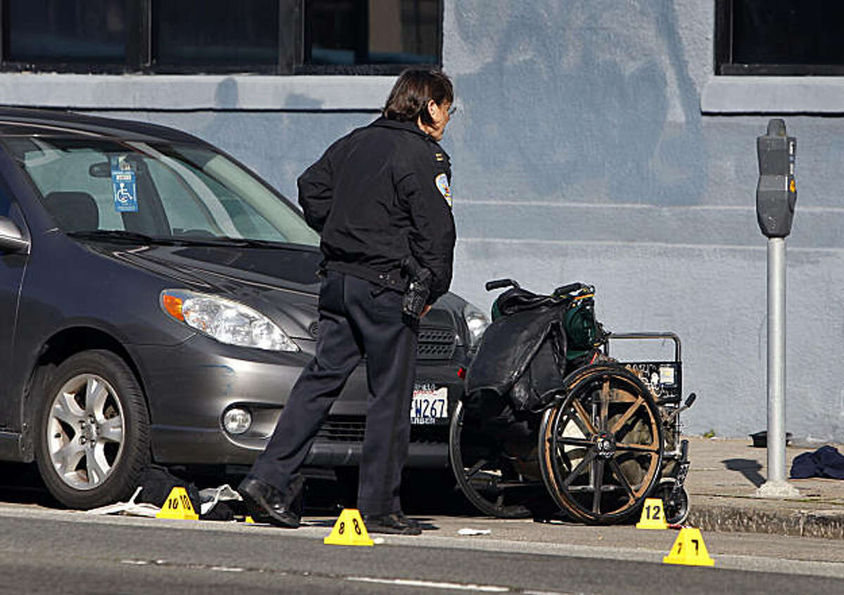 An officer looks at the scene after police shot a man in a wheelchair who reportedly threatened them with a knife in San Francisco, Calif., on Tuesday, Jan. 4, 2011. Witnesses say the man had earlier slashed the tires of several cars parked nearby.