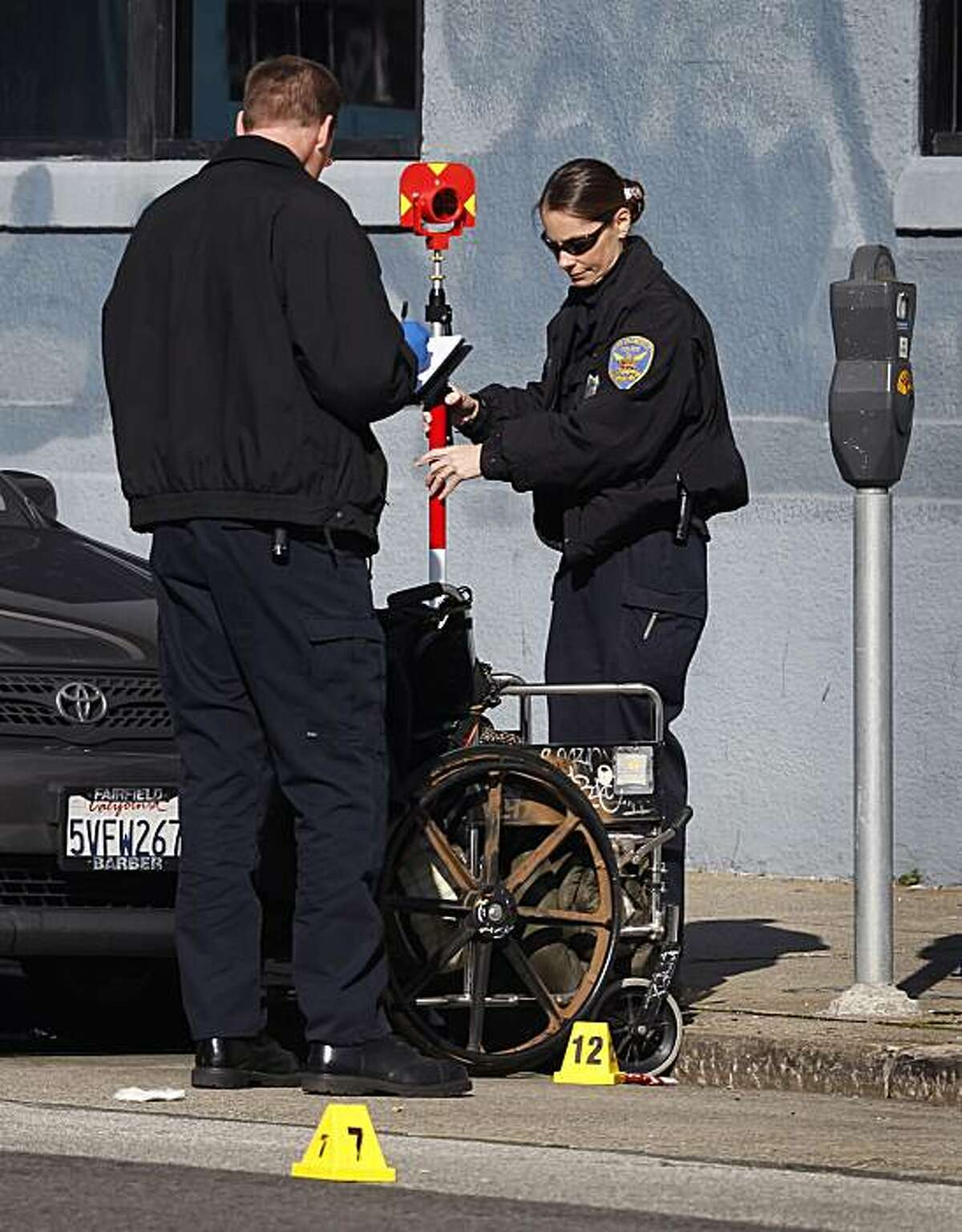 Crime scene investigators gather evidence after police officers shot a man in a wheelchair who reportedly threatened them with a knife in San Francisco, Calif., on Tuesday, Jan. 4, 2011. Witnesses say the man had earlier slashed the tires of several cars parked nearby.