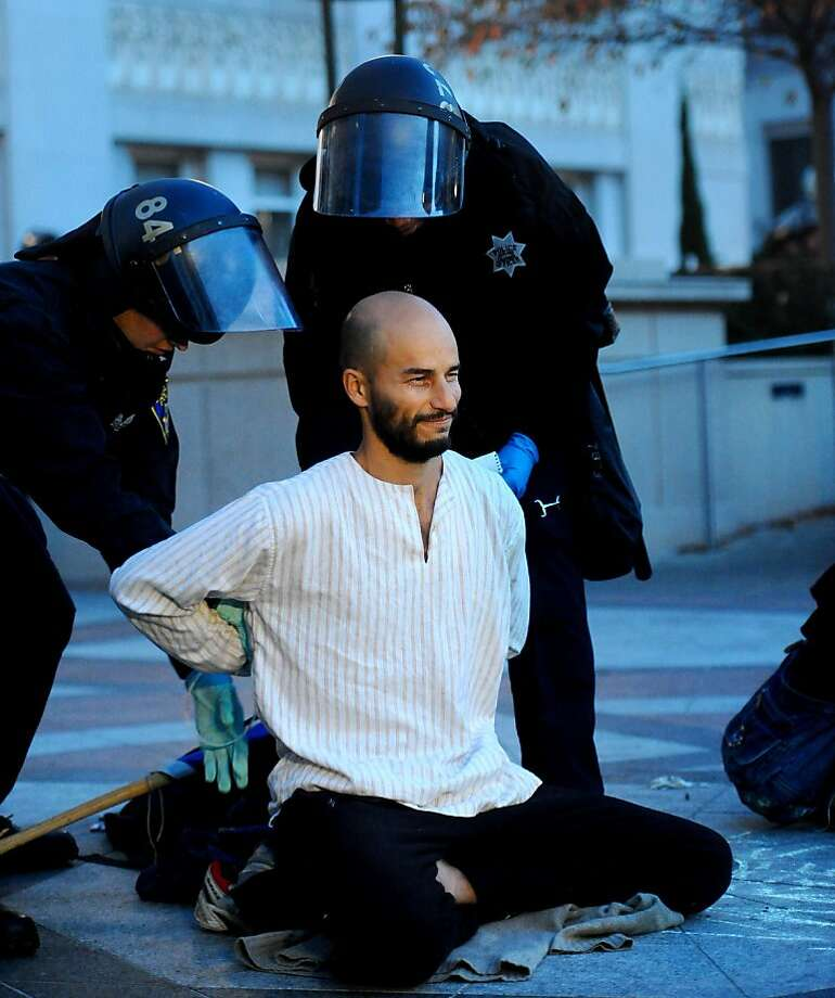 An Occupy Oakland protester meditates as police arrest him on Monday, Nov. 14, 2011, in Oakland, Calif. The man, who declined to leave voluntarily, was one of three people meditating in the group's general assembly meeting area as police took control of Frank Ogawa Plaza.      Ran on: 11-16-2011 Francisco &quo;Pancho&quo; Ramos Stierle meditates as police arrest him Monday. He had declined orders to leave. Photo: Noah Berger, Special To The Chronicle