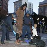 An Occupy Oakland protester is handcuffed to be detained as police officers take down tents of the Occupy Oakland encampment to evict protesters, who are camping at the Frank Ogawa Plaza in front of the Oakland City Hall, on November 14, 2011 in Oakland, California. Hundreds of police in riot gear swept into the Occupy Oakland site at dawn on Monday, an officer said, ordering protesters to leave the camp which has been a weeks-long source of tension for the west coast US city. AFP Photo/Kimihiro Hoshino (Photo credit should read KIMIHIRO HOSHINO/AFP/Getty Images)