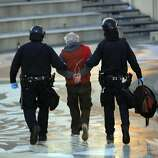 A protester is led away in handcuffs as police from various agencies moved in to clear out Occupy Oakland protesters and their tents from Frank Ogawa Plaza in Oakland, Calif., on Monday, November 14, 2011.