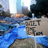 An sign declaring Occupy Oakland's quiet hours rises above leveled tents following a police raid on Monday, Nov. 14, 2011, in Oakland, Calif.