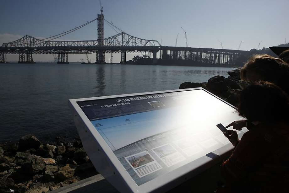 Visitors use their smart phones to scan QR codes printed on a new informational sign to mark the celebration of the San Francisco-Oakland Bay Bridge's 75th anniversary on Thursday, November 10, 2011 on Treasure Island in San Francisco, Calif. Photo: Beck Diefenbach, Special To The Chronicle