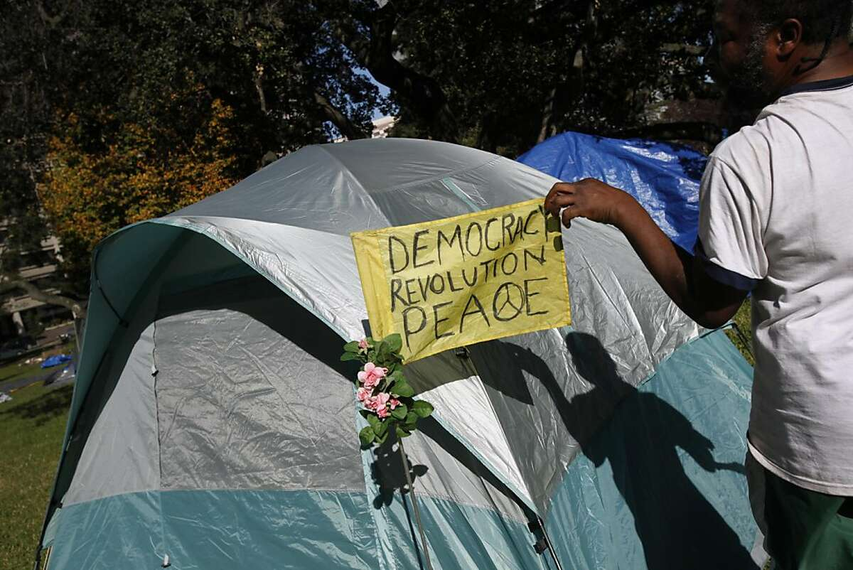 Manisl Roberson (cq) of Oakland shows off the flag on his tent at Snow Park in Oakland, Calif., Monday, November 14, 2011. Roberson relocated from Frank Ogawa Plaza before an early morning raid to dismantle the Occupy Oakland camp.