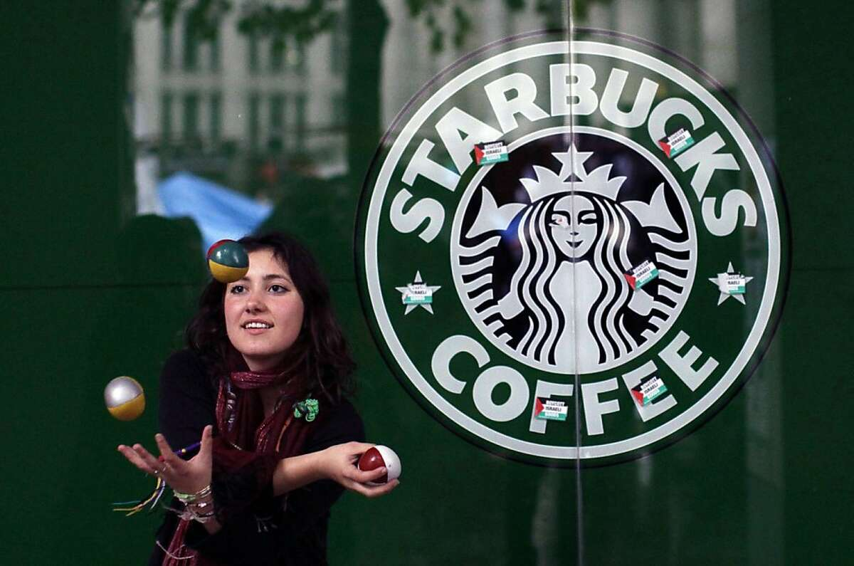 A French supporter of the Occupy London Stock Exchange movement who gave her name as Estelle de Marseille, stating that it's the name she goes by but not her real name, juggles outside a branch of the Starbucks coffee chain beside the protest camp outside St Paul's Cathedral London, Thursday, Oct. 27, 2011. St. Paul's Cathedral says it will reopen Friday, a week after is shut its doors because of an anti-capitalist protest camp outside. It will reopen to tourists on Saturday. Protesters have been camped outside the building since Oct. 15. Days later, cathedral officials shut the building to the public, saying the campsite was a health and safety hazard. (AP Photo/Matt Dunham) Ran on: 11-15-2011 Starbucks says it is removing a surcharge for bags of coffee beans that weigh less than a pound.
