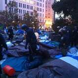 Police comb through the remains of the Occupy Oakland camp early on Monday, November 15, 2011 after raiding the camp, detaining protesters and tearing down tents. Police moved in to tear down the month-old encampment before dawn Monday.