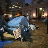 Police officers take down tents of the Occupy Oakland encampment to evict Occupy Oakland protesters, who are camping at the Frank Ogawa Plaza in front of the Oakland City Hall, on November 14, 2011 in Oakland, California. Hundreds of police in riot gear swept into the Occupy Oakland site at dawn on Monday, an officer said, ordering protesters to leave the camp which has been a weeks-long source of tension for the west coast US city. AFP Photo/Kimihiro Hoshino (Photo credit should read KIMIHIRO HOSHINO/AFP/Getty Images)